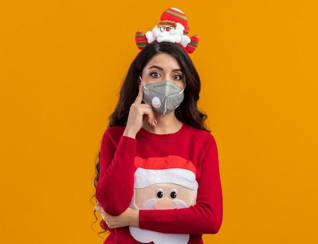 Premurosa giovane bella ragazza che indossa la fascia di babbo natale e maglione con maschera protettiva tenendo la mano sul mento isolato sulla parete arancione con spazio di copia