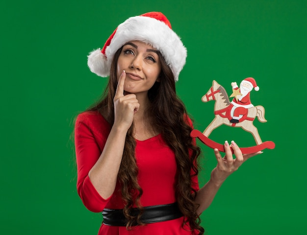 Thoughtful young pretty girl wearing santa hat holding santa on rocking horse figurine touching face looking up isolated on green background