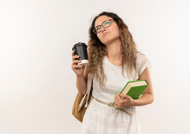 안경을 쓰고 사려 깊은 젊은 예쁜 여학생과 흰 벽에 고립 된 커피 컵과 책을 들고 올려 다시 가방