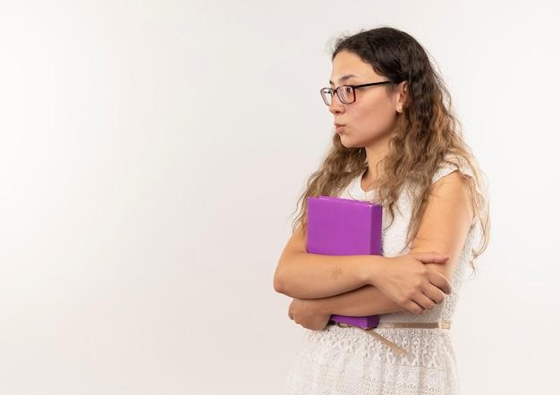 眼鏡とバックバッグを身に着けている思いやりのある若いかわいい女子高生は、白い壁に隔離された側を見て本を保持している縦断ビューに立っています