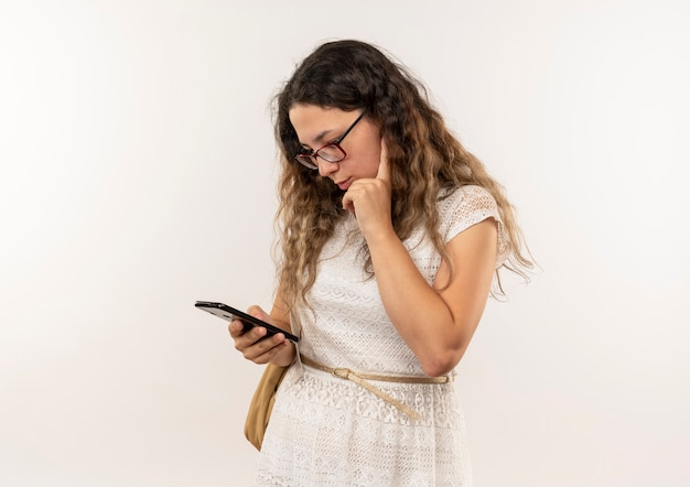 白い壁に隔離されたあごに手を置いて彼女の携帯電話を使用して眼鏡とバックバッグを身に着けている思いやりのある若いかわいい女子高生