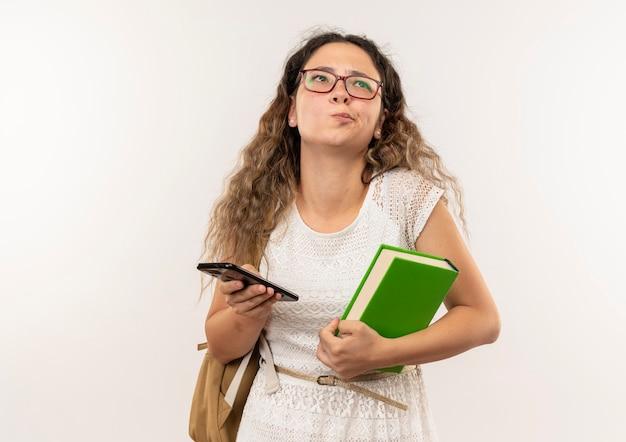 Riflessivo giovane studentessa graziosa con gli occhiali e borsa posteriore che tiene il libro e il telefono cellulare che osserva in su isolato sul muro bianco