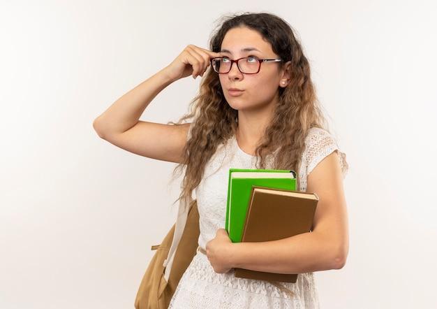 Riflessivo giovane studentessa graziosa con gli occhiali e borsa posteriore che tengono i libri che cercano di mettere il dito sul tempio isolato sul muro bianco