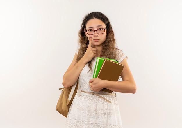 Giovane studentessa graziosa premurosa con gli occhiali e borsa posteriore che tengono i libri che mettono il dito sulla guancia isolata sulla parete bianca