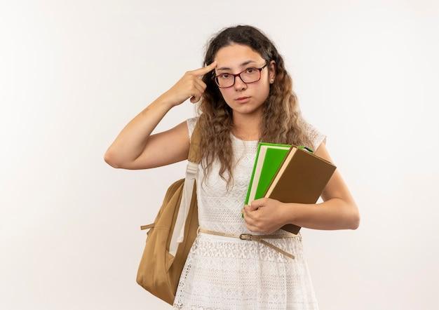 Riflessivo giovane studentessa graziosa con gli occhiali e borsa posteriore che tengono i libri che mettono il dito sulla testa guardando la parte anteriore isolata sul muro bianco