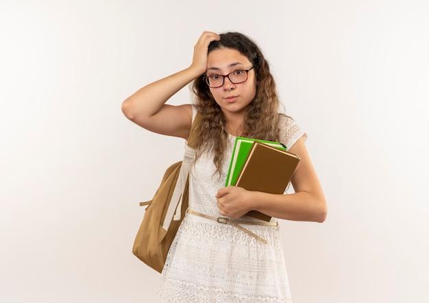 Riflessivo giovane studentessa graziosa con gli occhiali e borsa posteriore che tengono i libri mettendo la mano sulla testa isolata sulla parete bianca