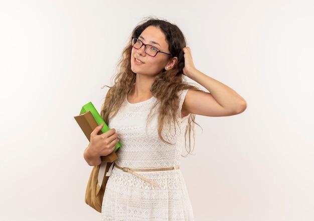 Riflessivo giovane studentessa graziosa con gli occhiali e borsa posteriore che tengono i libri mettendo la mano sulla testa guardando il lato isolato sul muro bianco