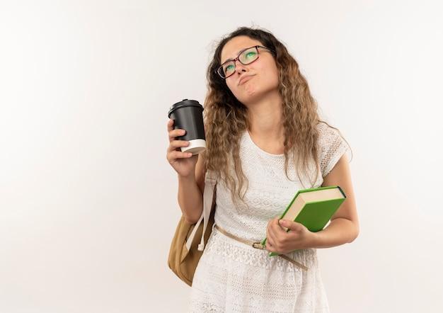 Giovane studentessa graziosa premurosa con gli occhiali e borsa posteriore che osserva in su che tiene tazza di caffè e libro isolato sulla parete bianca