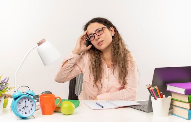 Riflessivo giovane studentessa graziosa con gli occhiali seduto alla scrivania con strumenti di scuola facendo i compiti guardando a lato con la mano sulla testa isolata sul muro bianco