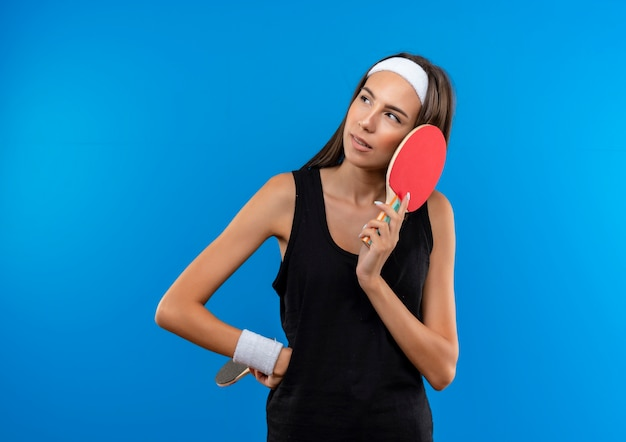 卓球のラケットを保持し、青いスペースで隔離された側を見て腰に手を置くヘッドバンドとリストバンドを身に着けている思いやりのある若いかなりスポーティーな女の子