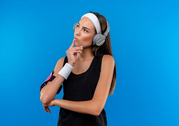 Premurosa giovane ragazza piuttosto sportiva che indossa la fascia e il braccialetto e le cuffie con fascia da braccio del telefono guardando a lato e mettendo la mano sul mento isolato su spazio blu