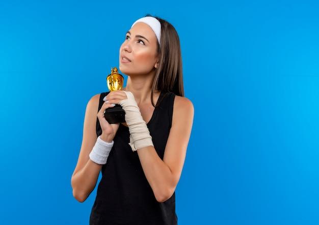 Premurosa giovane ragazza piuttosto sportiva che indossa la fascia e il braccialetto che tiene la tazza del vincitore con un polso ferito e avvolto con la benda che osserva in su isolato sullo spazio blu
