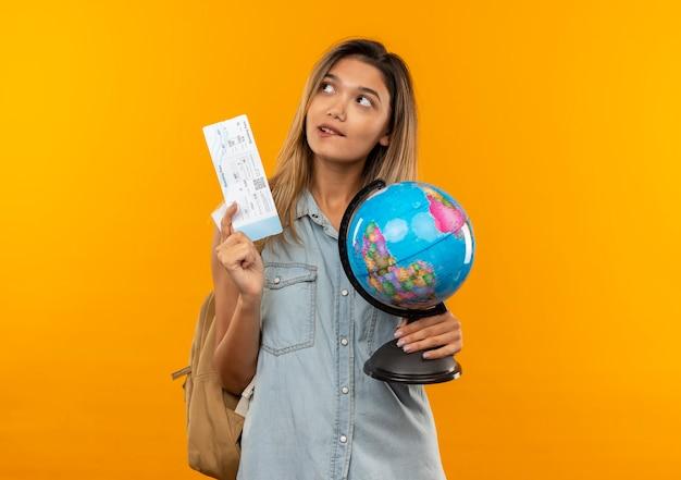 Premurosa giovane studentessa graziosa che indossa la borsa posteriore che tiene il biglietto aereo e il globo guardando il lato e mordendosi il labbro isolato sulla parete arancione