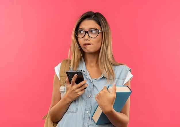 眼鏡とバックバッグを身に着けている思いやりのある若いかわいい学生の女の子は、携帯電話と本を横に見て、ピンクの壁に分離された唇を噛んでいます