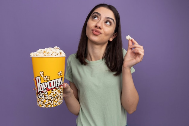 Premurosa giovane donna graziosa che tiene secchio di popcorn e pezzo di popcorn guardando in alto isolato sulla parete viola con spazio di copia