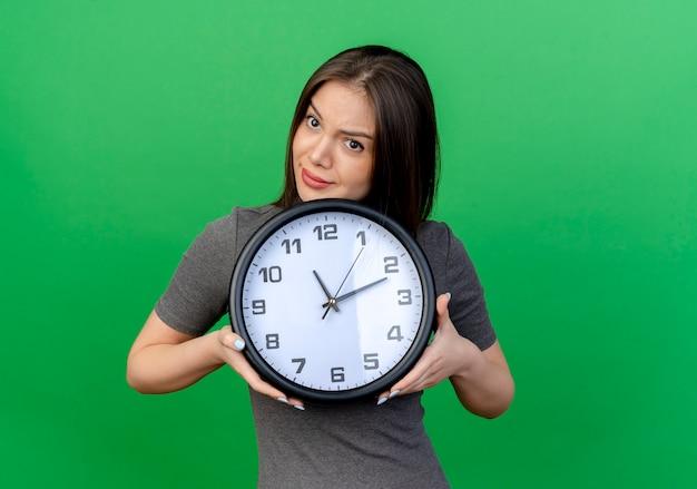 Riflessivo giovane donna graziosa che tiene orologio guardando lato isolato su sfondo verde con copia spazio