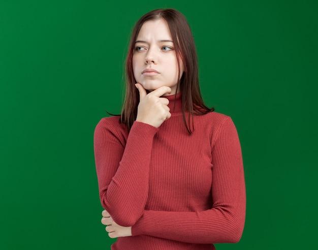 복사 공간이 있는 녹색 벽에 격리된 면을 바라보며 턱에 손을 대고 있는 사려 깊은 젊은 예쁜 여자