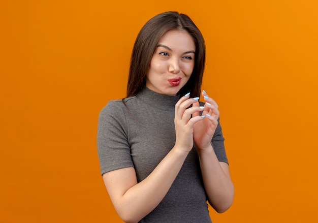복사 공간 오렌지 배경에 고립 된 똑바로보고 함께 손을 유지하는 사려 깊은 젊은 예쁜 여자