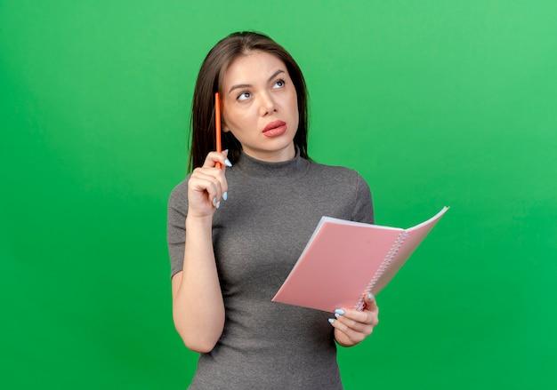 Задумчивая молодая красивая женщина трогает голову ручкой и держит открытый блокнот, глядя вверх изолированно на зеленом фоне с копией пространства