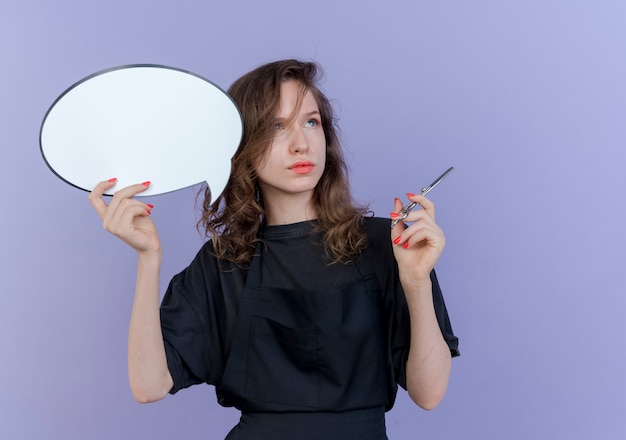 思いやりのある若いスラブ女性理髪師は、コピースペースと紫色の背景に分離された側を見てチャットバブルとはさみを保持している制服を着