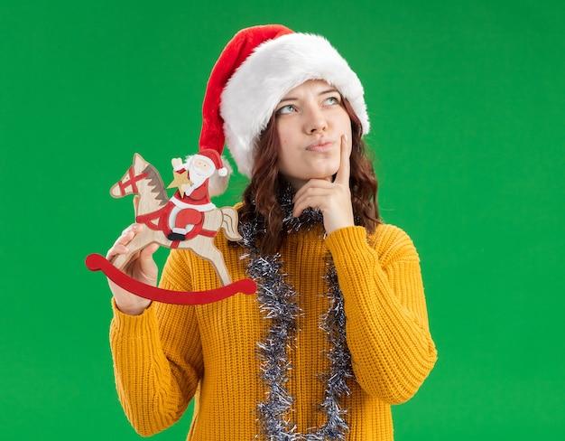 Задумчивая молодая славянская девушка в шапке санта-клауса и с гирляндой на шее кладет палец на подбородок и держит санта на украшении лошадки-качалки