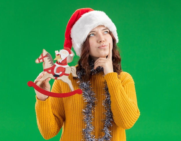 Thoughtful young slavic girl with santa hat and with garland around neck puts finger on chin and holds santa on rocking horse decoration