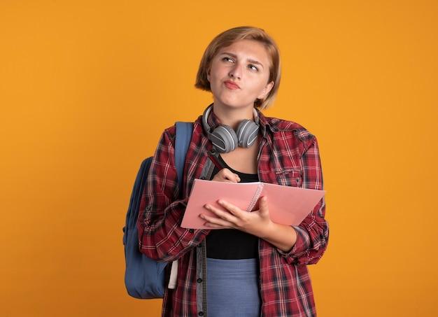 Una giovane studentessa slava premurosa con le cuffie che indossa lo zaino tiene la penna e il taccuino guardando a lato