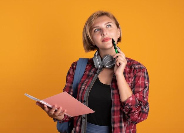 La giovane studentessa slava premurosa con le cuffie che indossa lo zaino tiene la penna e il taccuino