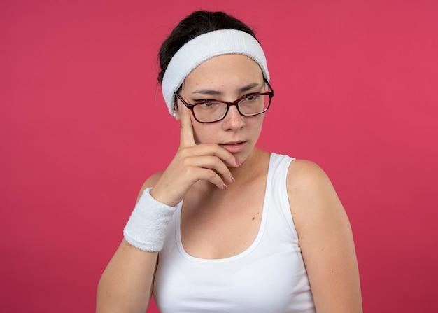 ヘッドバンドとリストバンドを身に着けた光学眼鏡をかけた思慮深いスポーティな少女が、あごに手を当てて下を向く