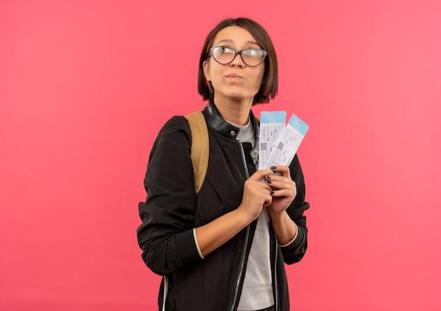 Задумчивая молодая студентка в очках и задней сумке с билетами на самолет смотрит в сторону, изолированную на розовой стене