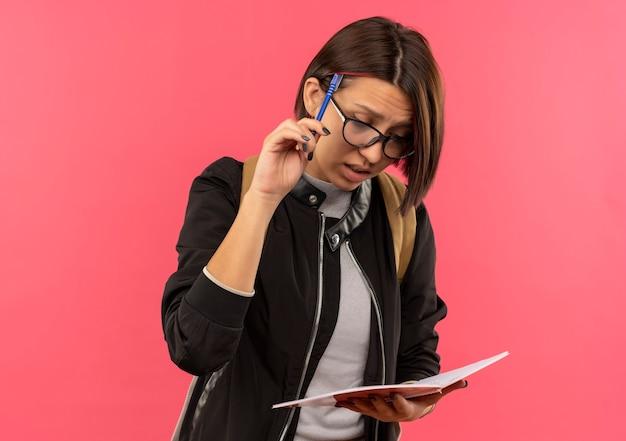 Задумчивая молодая студентка в очках и задней сумке держит и смотрит на блокнот, касаясь головы ручкой, изолированной на розовой стене