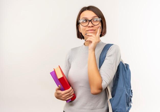 Задумчивая молодая студентка в очках и задней сумке, держащая книги, положив руку на подбородок, изолированную на белой стене