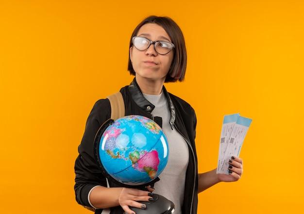 Задумчивая молодая студентка в очках и задней сумке держит глобус и билеты, глядя на сторону, изолированную на оранжевой стене