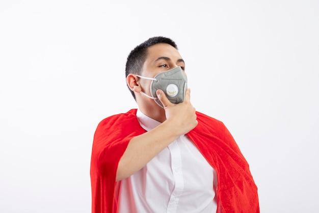 Задумчивый молодой мальчик-супергерой в красной накидке в защитной маске смотрит в сторону, держа руку на подбородке, изолированную на белом фоне с копией пространства