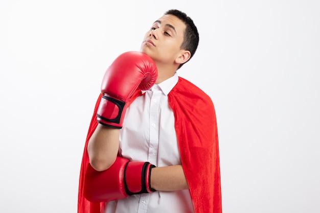 Riflessivo giovane supereroe ragazzo in mantello rosso che indossa i guanti di scatola guardando a lato mettendo la mano sul mento isolato su sfondo bianco con spazio di copia