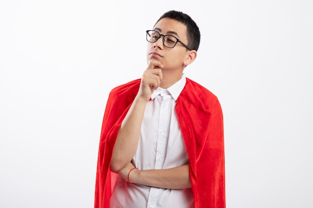 Thoughtful young superhero boy in red cape wearing glasses looking at side touching chin isolated on white background with copy space