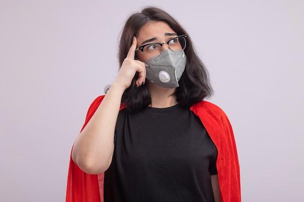 眼鏡と保護マスクを身に着けている赤いマントの思いやりのある若いスーパーヒーローの女性は、白い壁に分離された思考ジェスチャーをしている側を見て