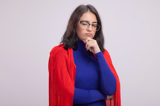 Considerato giovane supereroe donna in mantello rosso con gli occhiali tenendo la mano sul mento guardando verso il basso isolato sul muro bianco con spazio di copia