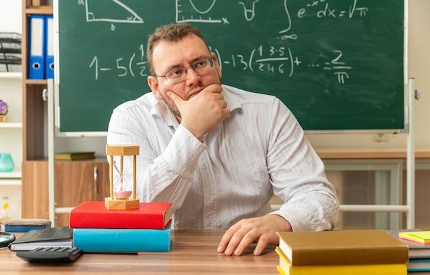 Premuroso giovane insegnante con gli occhiali seduto alla scrivania con materiale scolastico in classe tenendo la mano sul mento e sulla scrivania guardando a lato
