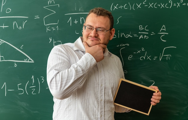 Thoughtful young teacher wearing glasses standing in front of chalkboard in classroom holding mini blackboard keeping hand on chin looking at side