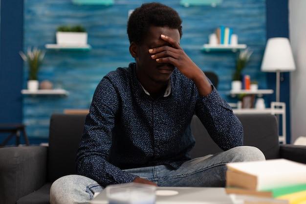 学校のコースの管理のアイデアを反映して大学のプログラムで考えている思いやりのある若いティーンエイジャー。考えているリビングルームのソファに座っている強調されたアフリカ系アメリカ人の男