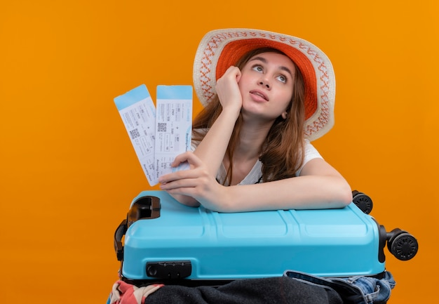 飛行機のチケットを保持し、孤立したオレンジ色の壁のスーツケースに腕を置く帽子をかぶって思いやりのある若い旅行者の女の子