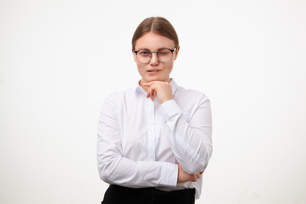 Thoughtful young white-headed woman with natural makeup touching her chin with raised hand while looking pensively at camera and biting underlip, isolated over white background