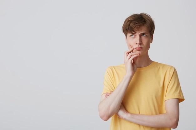 Il giovane studente maschio bianco premuroso tiene la sua mano sul mento, indossa la maglietta luminosa gialla, guarda da parte con un'espressione facciale concentrata pensa al suo futuro. isolato su muro bianco