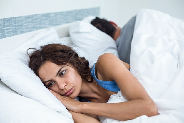 Вдумчивый молодая женщина, кроме мужа, лежа на кровати