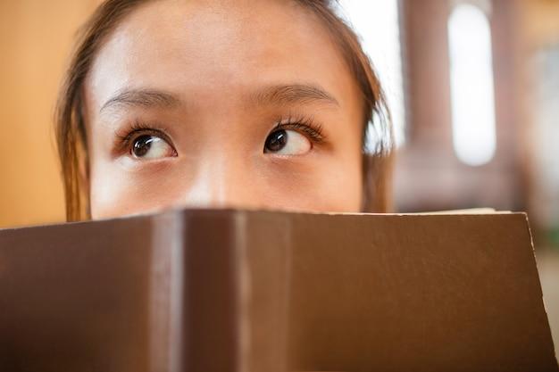思いやりのある若い女性は本で顔を覆う