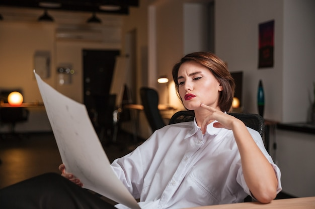 Thoughtful young woman fashion designer looking at sketches and thinking in office