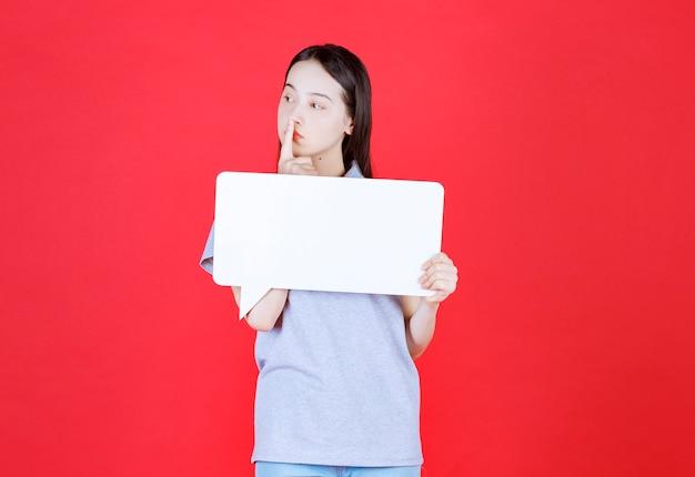 Задумчивая молодая женщина держит доску и смотрит в сторону