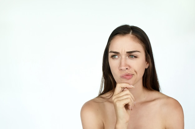 Thoughtful young woman holds fingers on her chin standing on white background