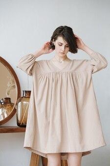 ベージュのドレスを着た思いやりのある若い女性が髪を固定し、スカートが袖で持ち上げられています。丸い鏡のあるテーブルの隣にある、屋内で短い髪の美しいブルネット